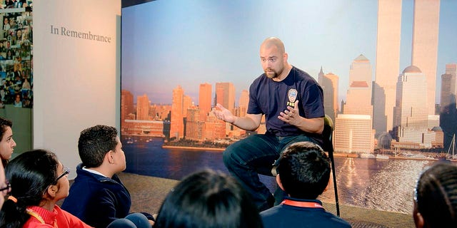 """This image released by HBO shows a New York City Fireman speaking to children in a scene from the documentary """"What Happened on September 11,"""" a short film directed at young people to explain to them what happened on Sept. 11, 2001. The program debuts on Wednesday."""