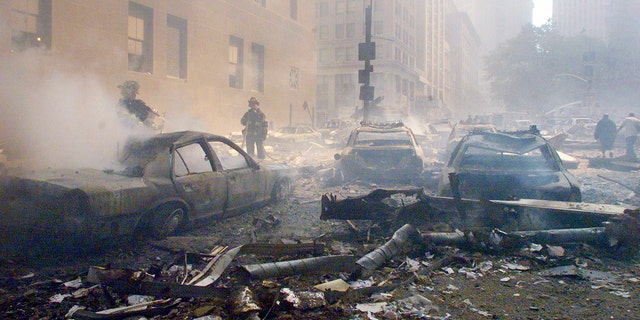 Cars smoulder in the street as the destroyed World Trade Center burns in New York on September 11, 2001. Two hijacked commercial planes slammed into the twin towers of the World Trade Center causing both 110-story landmarks to collapse in thunderous clouds of fire and smoke. REUTERS/Peter Morgan