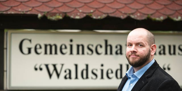 In this Sunday, Sept. 8, 2019 photo German far right party member Stefan Jagsch stands in front of the community house in the Altenstadt-Waldsiedlung, a part of the village of Altenstadt, near Frankfurt, Germany.