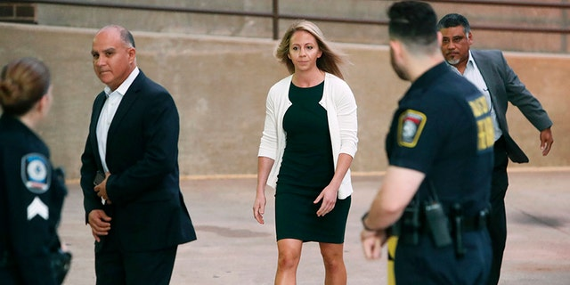 Former Dallas police officer Amber Guyger is escorted by a security detail as she arrives for her murder trial at the Frank Crowley Courthouse in downtown Dallas, Tuesday, Sept. 24, 2019.