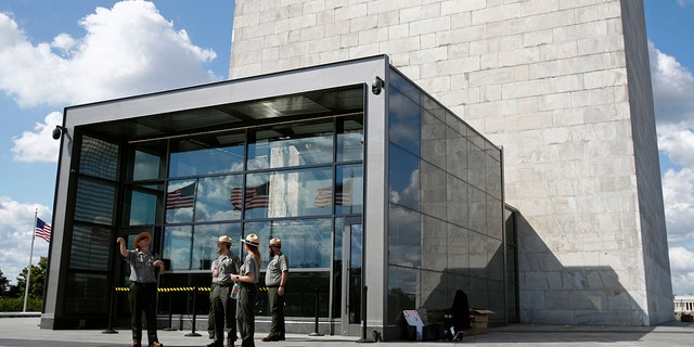 National Parks Service park rangers gather outside a new security screening building at the foot of the Washington Monument during a preview tour ahead of the monument's official reopening Wednesday Sept. 18 2019 in Washington. The monument which has