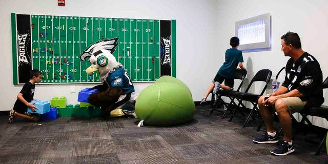 In this Thursday, Aug. 22, 2019, photo, Victor Ykoruk, right, watches as his 10-year-old twin sons, Ryan, left, and Jack, play in the Lincoln Financial Field sensory room, before a preseason NFL football game between the Philadelphia Eagles and the Baltimore Ravens in Philadelphia. (AP Photo/Matt Rourke)