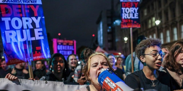 Protesters outside the House of Commons in London on Tuesday. (AP Photo/Vudi Xhymshiti)