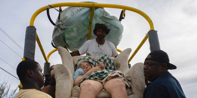 Sitting in her home's lounger, Virginia Mosvold, 84, is lowered from a truck by volunteers after being rescued from her flooded home on Ol' Freetown Farm farm in the aftermath of Hurricane Dorian before being taken to the hospital on the outskirts of Freeport, Bahamas, Wednesday, Sept. 4, 2019. (AP Photo/Ramon Espinosa)