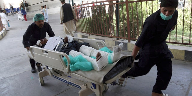 An injured man is carried into a hospital after a car bomb explosion in Kabul, Afghanistan, Thursday