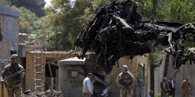 Resolute Support (RS) forces remove a damaged vehicle after a car bomb explosion in Kabul, Afghanistan.