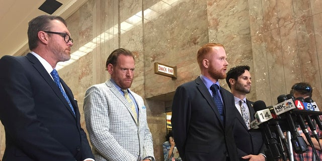 Attorney James Mulgannon, second from right, speaking at the courthouse with fellow attorney Tyler Smith, right, and Curtis Briggs, second from left, in Oakland on Thursday. (AP Photo/D. Ross Cameron)