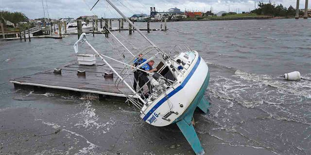 Beaufort Police Officer Curtis Resor, left, and Sgt. Michael Stepehens check a sailboat for occupants in Beaufort, N.C. after Hurricane Dorian passed the North Carolina coast on Friday, Sept. 6, 2019. (AP Photo/Tom Copeland)