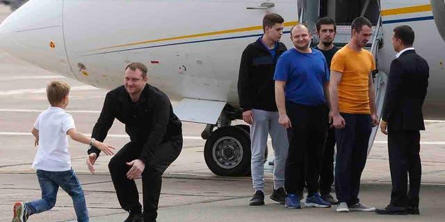 Ukraine's President Volodymyr Zelenskiy right greets Ukrainian prisoners upon their arrival at Boryspil airport outside Kyiv Ukraine Saturday Sept. 7 2019