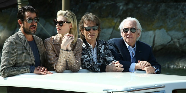 Actors Claes Bang, from left, Elizabeth Debicki, Mick Jagger or Donald Sutherland pose for photographers upon arrival for the photo call of the film 'The Burnt Orange Heresy'
