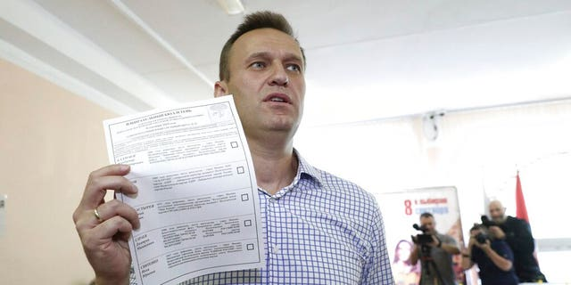Alexei Navalny shows his ballot as he arrives to vote during a city council election in Moscow on Sunday.