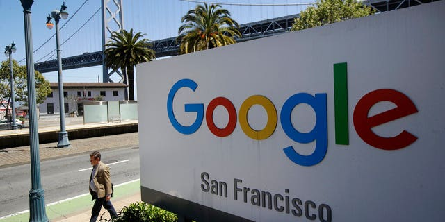 FILE - In this May 1, 2019, file photo a man walks past a Google sign outside with a span of the Bay Bridge at rear in San Francisco. A group of states are expected to announce an investigation into Google on Monday, Sept. 9, to investigate whether the tech company has become too big. (AP Photo/Jeff Chiu, File)