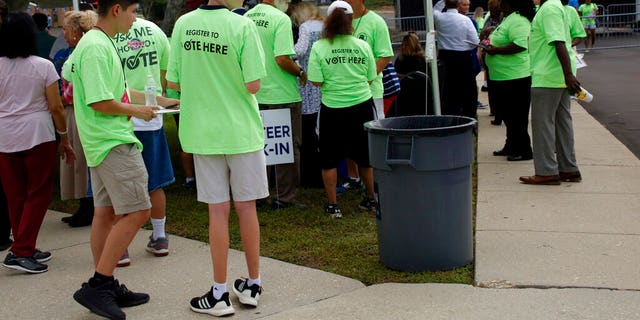 Voter registration workers gather before President Donald Trump's campaign rally in Fayetteville, N.C., Monday Sept. 9, 2019 (AP Photo/Chris Seward)
