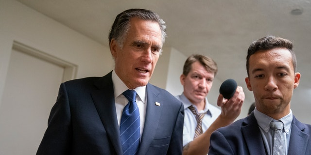 Sen. Mitt Romney, R-Utah, takes questions from reporters as he arrives for votes on pending nominations, at the Capitol in Washington, Wednesday, Sept. 11, 2019.