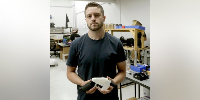 Cody Wilson holds a 3D-printed gun called the Liberator at his shop in Austin, Texas, last year. (AP Photo/Eric Gay, File)