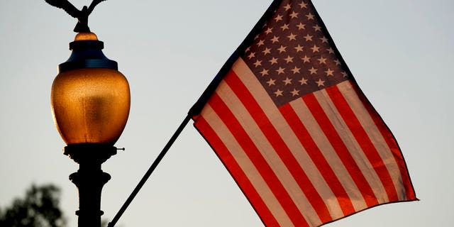 Flags fly at sunset with 51 instead of the usual 50 stars, along Pennsylvania Avenue, part of a display in support of statehood for the District of Columbia.