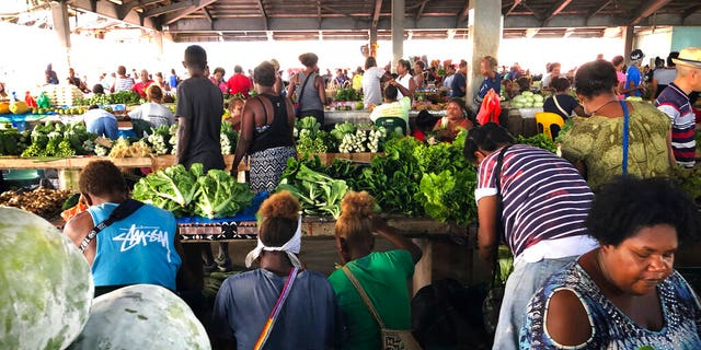 Customers shop for vegetables at the Honiara Central Market in Honiara, the capital of the Solomon Islands.