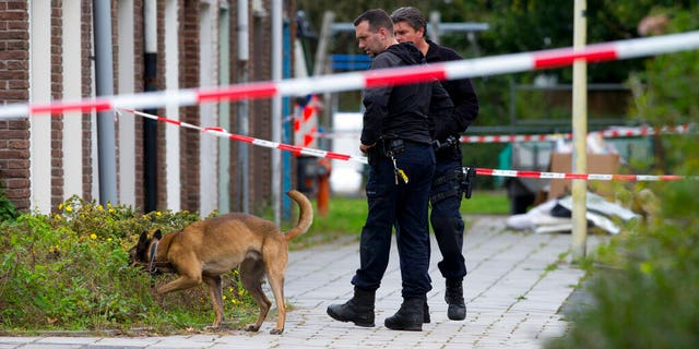 Forensic experts with a dog search for evidence in the area where a lawyer who represented a key witness in a major Dutch organized crime trial was gunned down in Amsterdam, in Amsterdam, Netherlands, Wednesday, Sept. 18, 2019.