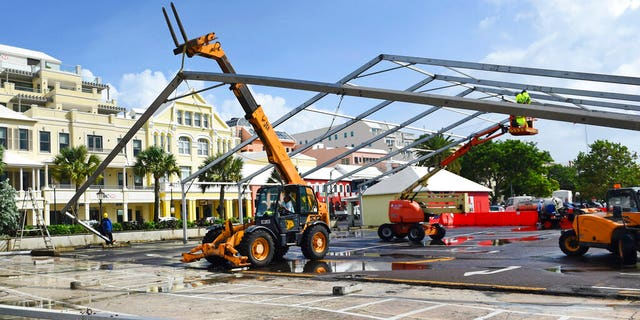 Workers take down a tent frame in preparation for Hurricane Humberto in Hamilton, Bermuda, Wednesday, Sept. 18, 2019.