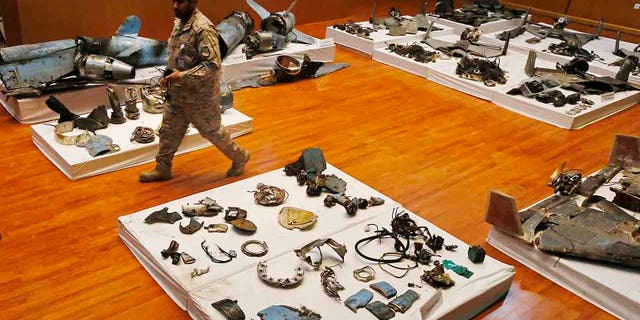 A Saudi military officer walks by what was described asa the remains of Iranian cruise missiles and drones used in an attack this weekend that targeted the heart of Saudi Arabia's oil industry, during a press conference by military spokesman Col. Turki al-Malki in Riyadh, Saudi Arabia, Wednesday, Sept. 18, 2019. Though Yemen's Houthi rebels claimed the assault, the U.S. alleges Iran was behind it. (AP Photo/Amr Nabil)