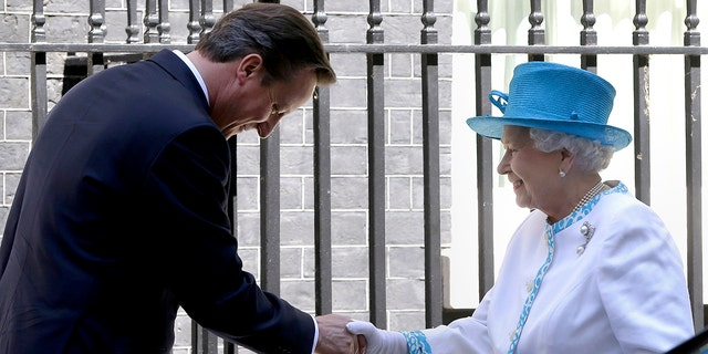 In this Tuesday, July 24, 2012 file photo, Britain's Queen Elizabeth II is greeted by Britain's Prime Minister David Cameron, as she arrives for lunch at Downing Street in London.
