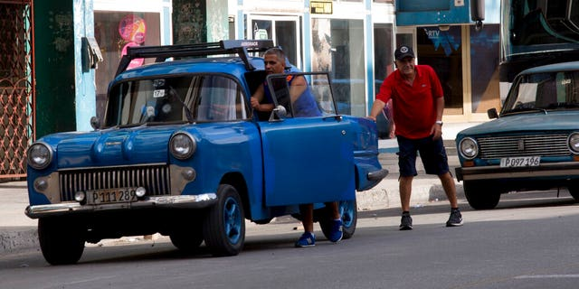 A drives pushes his vehicle to a gas station in Havana, Cuba, Thursday, Sept. 19. Increasingly, gas stations are running out with people still waiting in line.