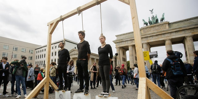 Three persons stand on ice blocks under gallows to protest against the climate policy prior to a 'Friday for Future' climate protest in front of the Brandenburg Gate in Berlin, Germany, Friday, Sept. 20, 2019.