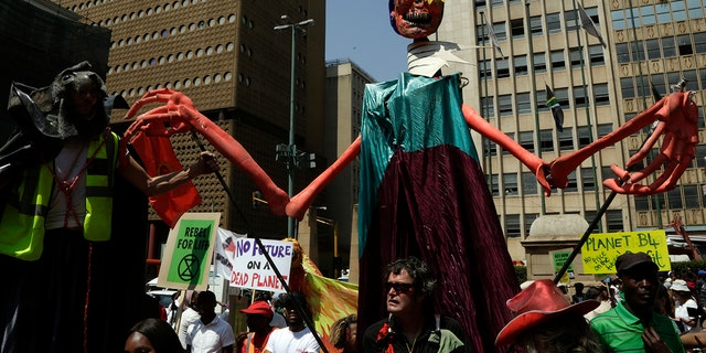 Climate protesters demonstrate outside the local government legislature's offices in Johannesburg, South Africa, Friday, Sept. 20, 2019. Protesters around the world joined rallies on Friday as a day of worldwide demonstrations calling for action against climate change began ahead of a U.N. summit in New York.
