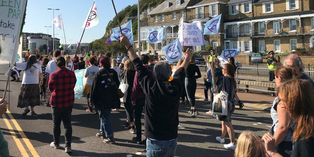 """Extinction Rebellion protesters occupy one side of a dual carriageway at the port of Dover, England, Saturday Sept. 21, 2019. Traffic around the Port of Dover, England's major sea connection with France, has been disrupted as a result of a protest by environmental activists. Activists from Extinction Rebellion said their protest around the port is intended to """"highlight the vulnerability of the U.K.'s food supply in the face of the ecological and climate emergency."""" (Michael Drummond/PA via AP)"""