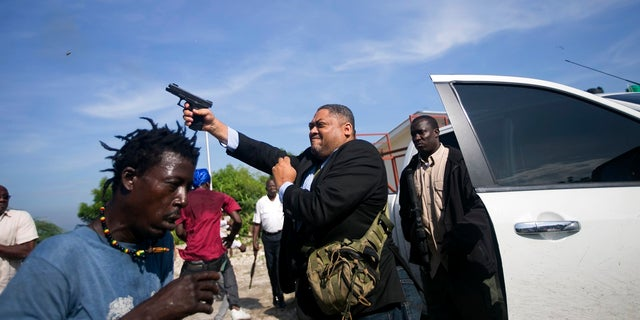 Ruling party Sen. Ralph Fethiere fires his gun outside Parliament as he arrives for a ceremony to ratify Fritz William Michel's nomination as prime minister. (AP Photo/Dieu Nalio Chery)