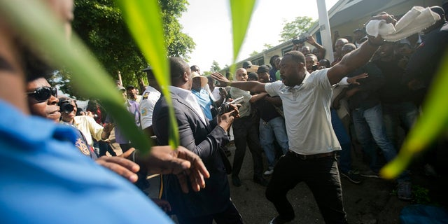 """An opposition protester holds out his arms and yells, """"Kill me"""" to ruling party Senator Willot Joseph. (AP Photo/Dieu Nalio Chery)"""