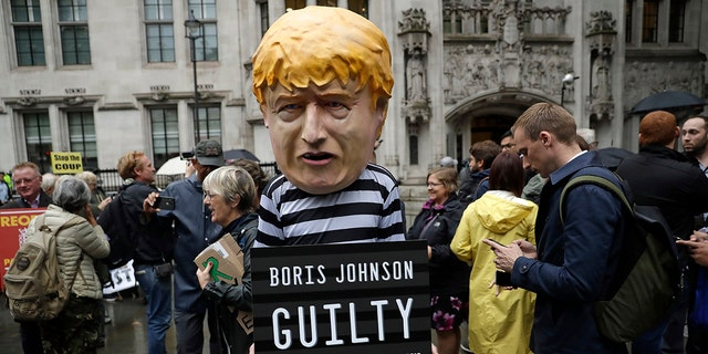 A person dressed as a caricature of British Prime Minister Boris Johnson in a prison uniform stands outside the Supreme Court in London, Tuesday, Sept. 24, 2019. (AP Photo/Matt Dunham)