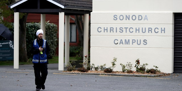 A security guard keeps watch outside student accommodation at Canterbury University in Christchurch, New Zealand, Wednesday, Sept. 25, 2019. (AP Photo/Mark Baker)