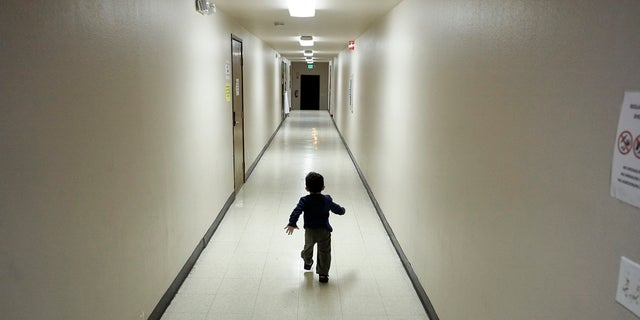 In this Dec. 11, 2018, photo, an asylum-seeking boy from Central America runs down a hallway after arriving at a San Diego, Calif., shelter from an immigration detention center (AP Photo/Gregory Bull, File)