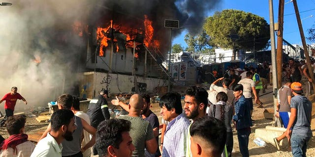 Migrants and refugees stand next to burning house containers at the Moria refugee camp, on the northeastern Aegean island of Lesbos, Greece, Sunday, Sept. 29, 2019.