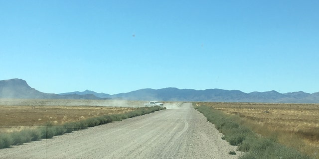 Dust from an unmarked white truck can be seen in a back road near one of the entrances to Area 51 near Rachel, Nev.