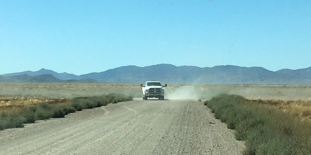 "An unmarked white truck turns from a side road onto the roadway to Area 51's so-called ""back gate"" on Wednesday."