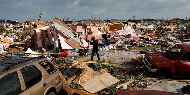 A man walks among debris at the Mudd neighborhood, devastated after Hurricane Dorian hit the Abaco Islands in Marsh Harbour, Bahamas, September 6, 2019. (REUTERS/Marco Bello)
