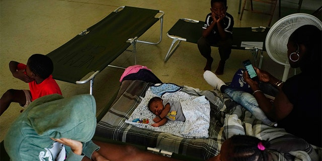 Anastacia Makey, 43, far right, looks at her phone as she and her family sits on cots with other residents inside a church that was opened up as a shelter as they wait out Hurricane Dorian in Freeport on Grand Bahama, Bahamas, on Sunday.
