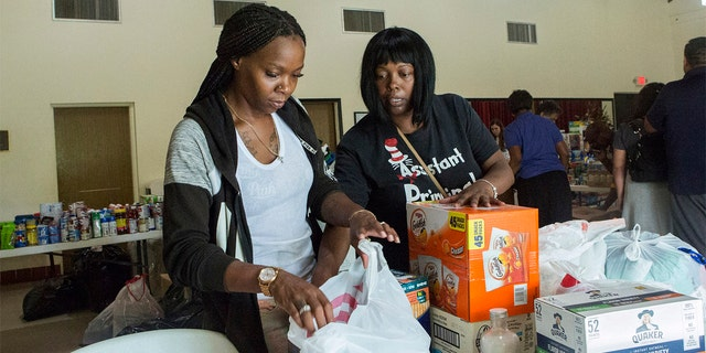 Volunteers Jazz Williams, 29, left, and Jodye Scavella, 47, organizing donated goods for those affected by Hurricane Dorian in the Bahamas, at Christ Episcopal Church in Miami on Tuesday. (AP Photo/Ellis Rua)