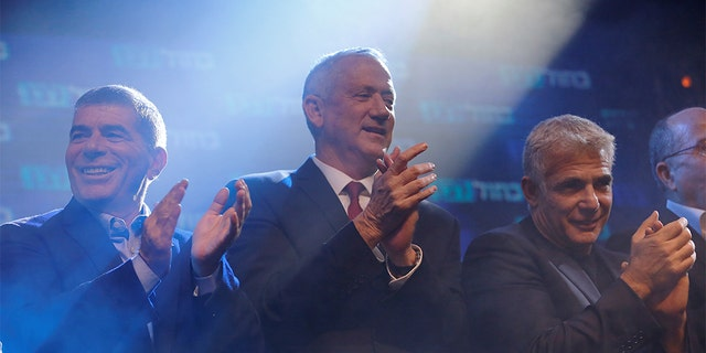 Blue and White party leader Benny Gantz, center and co-leaders Yair Lapid, right and Gaby Ashkenazi reacting at the party's headquarters early Wednesday.