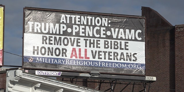 A billboard calling on President Trump, Vice President Pence, and the VA to take the Bible out of the hospital on display in downtown Manchester, N.H.