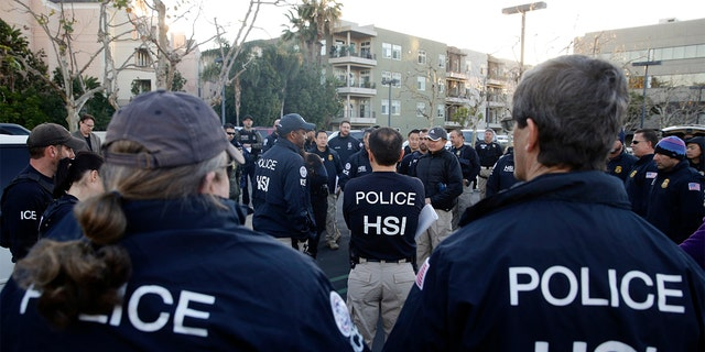 Federal agents gathering at a parking lot before raiding an upscale apartment complex linked to a birth tourism business in Irvine, Calif., in 2015.