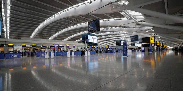 Terminal 5 at Heathrow Airport, which handles British Airways flights, stands virtually empty of passengers as staff on Monday morning.