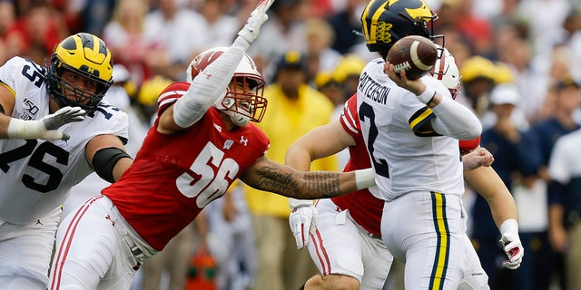 Wisconsin defensive end Rodas Johnson (56) goes after Michigan quarterback Shea Patterson (2) during the first half of an NCAA college football game Saturday, Sept. 21, 2019, in Madison, Wis. (AP Photo/Andy Manis)
