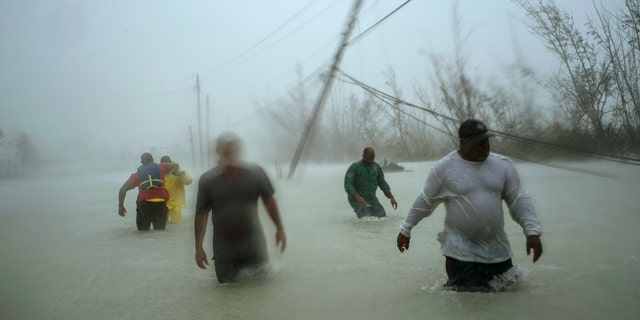 Volunteers walk under the wind and rain from Hurricane Dorian through a flooded road as they work to rescue families near the Causarina bridge in Freeport, Grand Bahama, Bahamas, Tuesday,