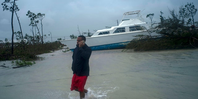 A man talks on his mobile phone next to a catamaran that was thrown onshore by the Hurricane Dorian near highway close Freeport, Grand Bahama, Bahamas, Tuesday Sept. 3, 2019.