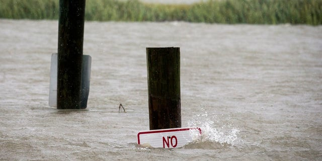 A sign at the Lazaretto Creek boat ramp as is nearly underwater at high tide as Hurricane Dorian makes its way up the east coast, Wednesday, Sept. 4, 2019, toward Tybee Island, Ga.