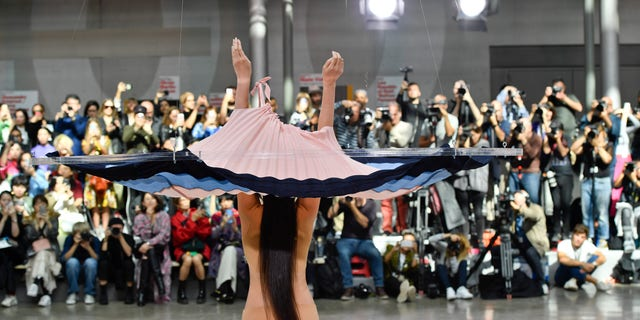 A model on the runway during the Issey Miyake Ready to Wear Spring/Summer 2020 fashion show as part of Paris Fashion Week. The dress was dropped on the model using a pulley system.