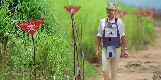 Princess Diana, wearing armor and a visor, visits a landmine minefield being cleared by the charity Halo in Huambo, Angola.